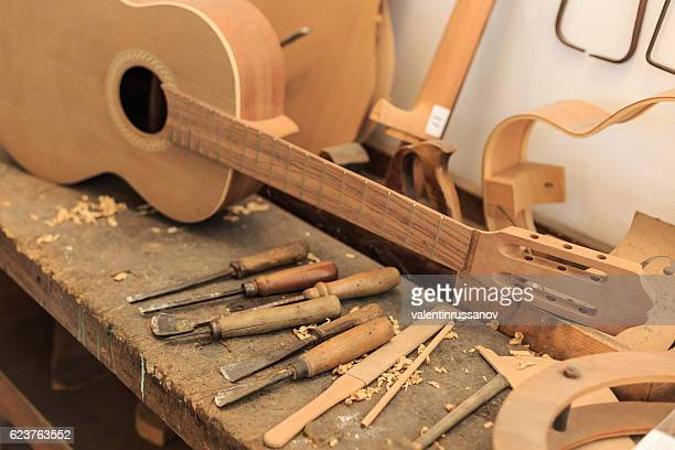 Unfinished acustic guitar and tools in workshop