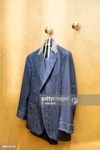 unfinished bespoke jacket hanging in tailors shop - custom tailored suit stock pictures, royalty-free photos & images