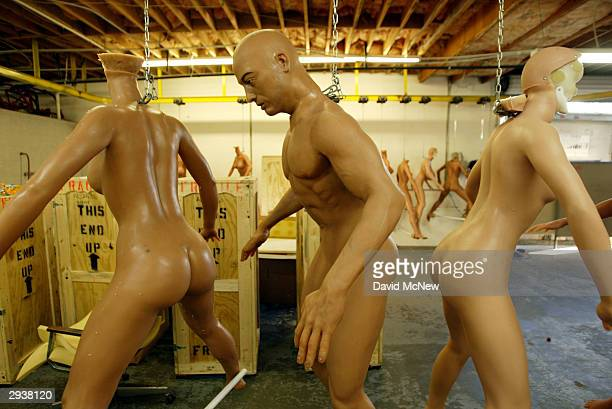 Unfinished silicone RealDoll sex dolls hang from chains at the Abyss Creations factory on February 5 2004 in San Marcos California RealDolls are...