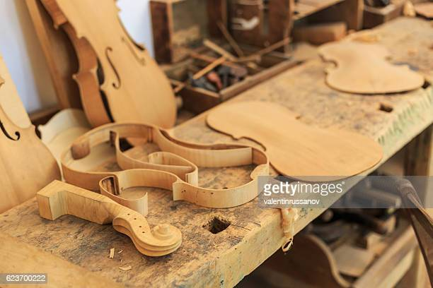 Unfinished violin and wooden tools in workshop
