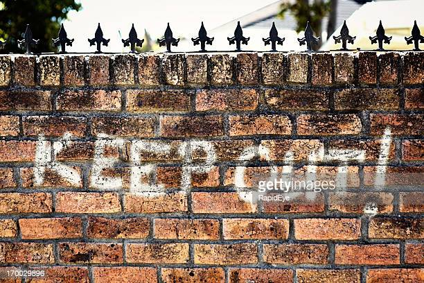 """Unfriendly graffiti on wall with spiked top says """"KEEP OUT!"""""""