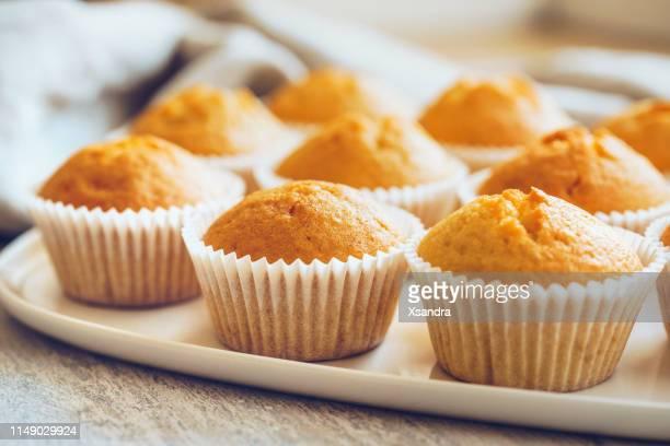 los cupcakes sin escarcha en una placa blanca - cupcake fotografías e imágenes de stock