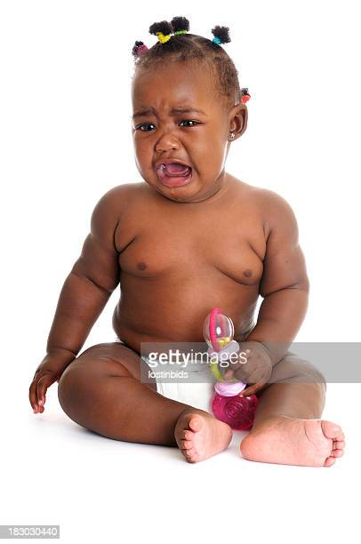 Unhappy African American Baby Girl Crying While Holding A Rattle