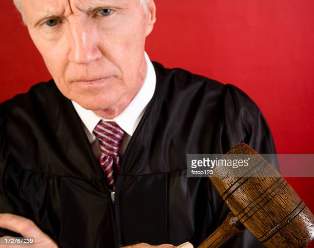 Unhappy, angry man judge in black robe with wooden gavel.