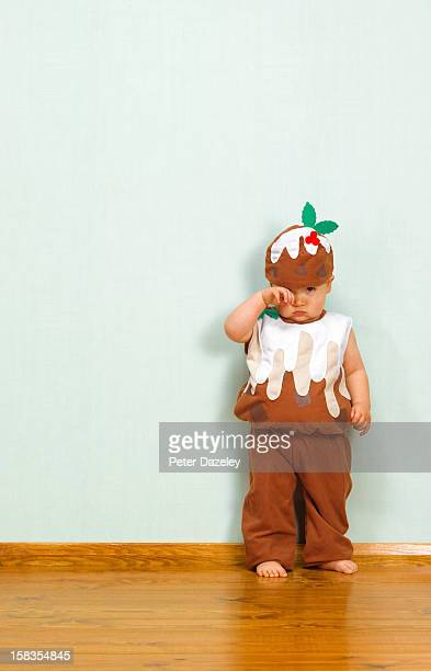 Unhappy baby boy in christmas pudding outfit
