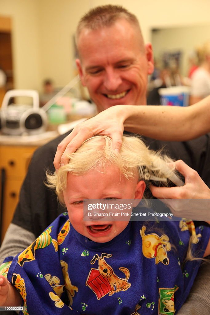 Unhappy Baby Getting First Haircut At Barber Shop Stock Photo
