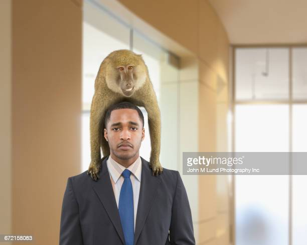 Unhappy Black businessman with grinning monkey on back