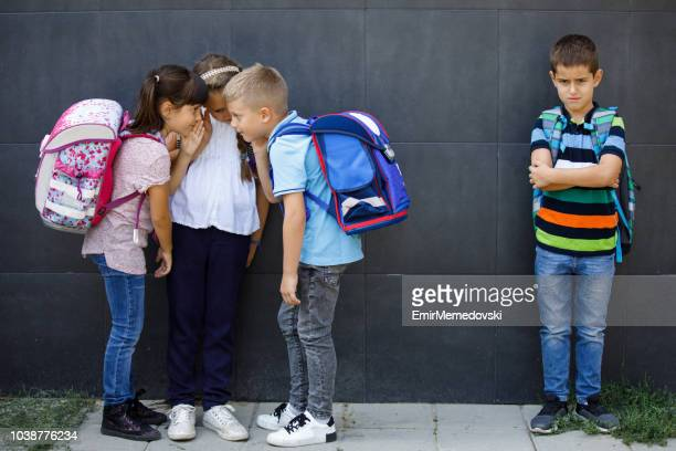 unhappy boy being gossiped about by school friends - bullying imagens e fotografias de stock
