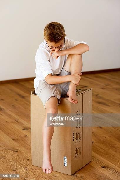 Unhappy boy sitting on cardboard box in an empty room