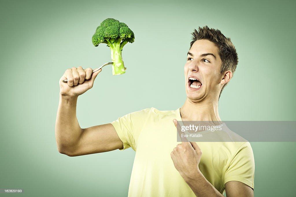 Unhappy boy with a broccoli : Stock Photo