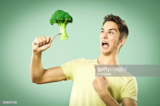 Unhappy boy with a broccoli