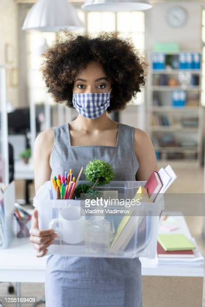 unhappy business woman with surgical medical mask going out with box container, looking at camera and feeling looser. - quitting a job stock pictures, royalty-free photos & images