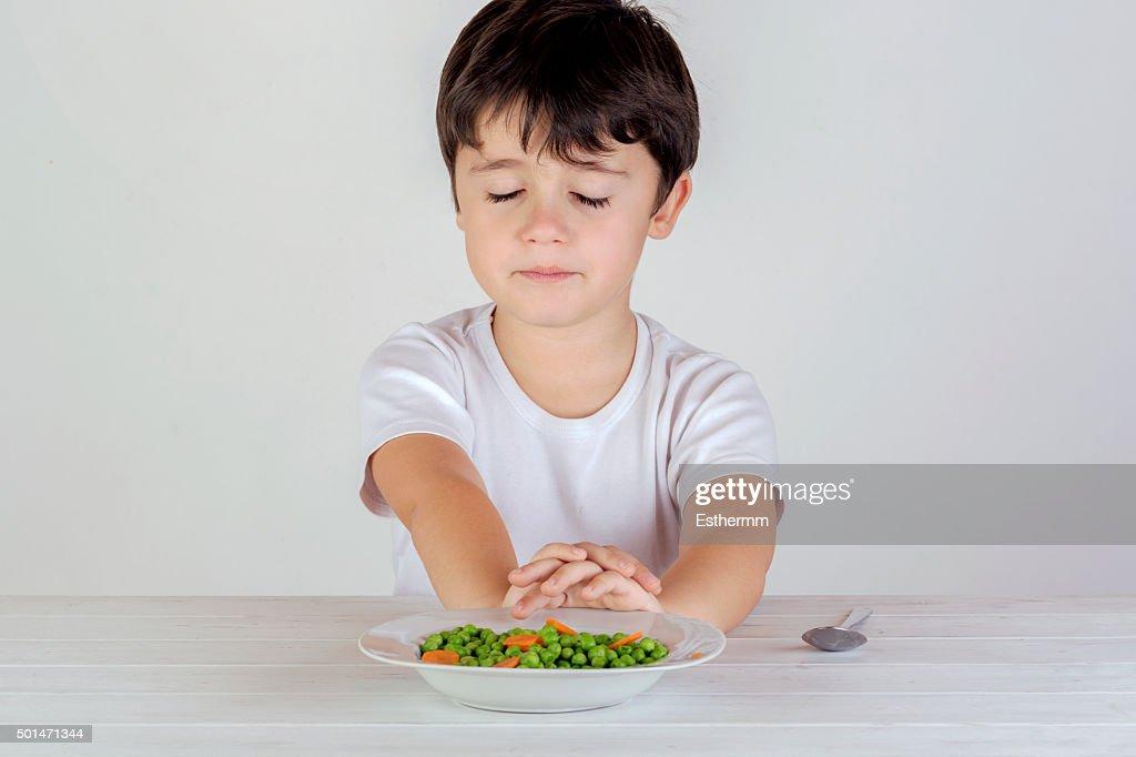 Unhappy Caucasian boy eating vegetables : Stock Photo