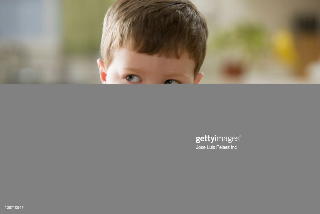 Unhappy Caucasian boy sitting at dinner table : Stock Photo