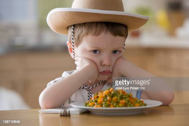 unhappy caucasian boy sitting at dinner table - sulking stock pictures, royalty-free photos & images