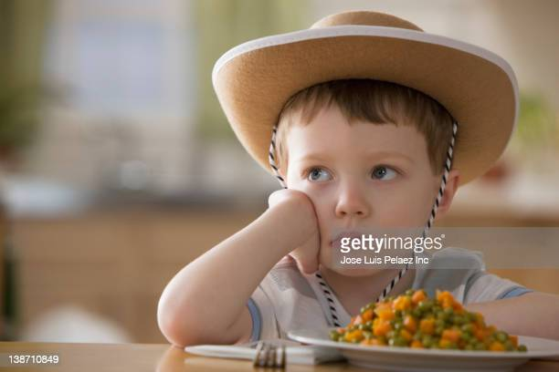 Unhappy Caucasian boy sitting at dinner table