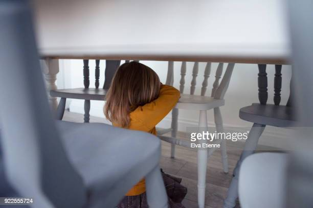 unhappy child (4-5) hiding under a dining table - tantrum stock photos and pictures