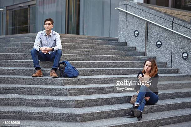 Unhappy couple sitting apart on steps
