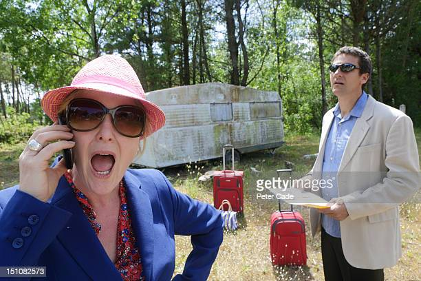 Unhappy couple with suitcases and run down caravan