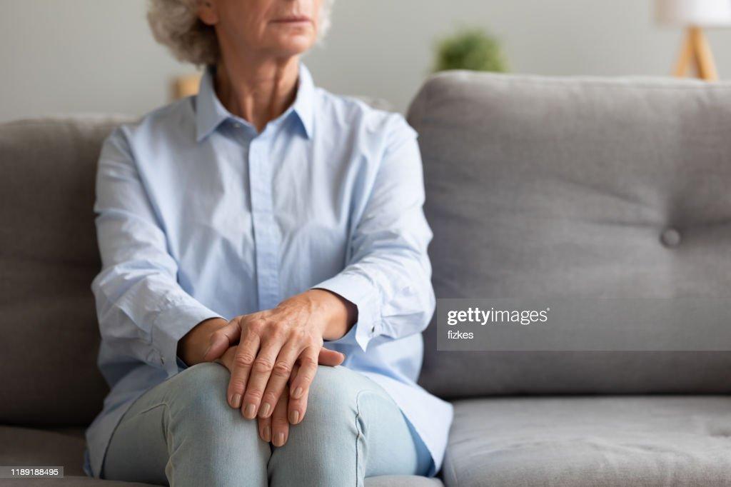 Unhappy depressed senior woman sit alone on sofa, closeup view : Stock Photo