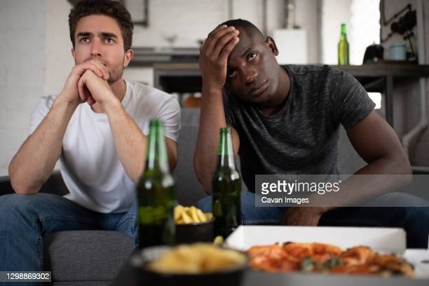 unhappy diverse friends watching disappointing football match - failure stock pictures, royalty-free photos & images