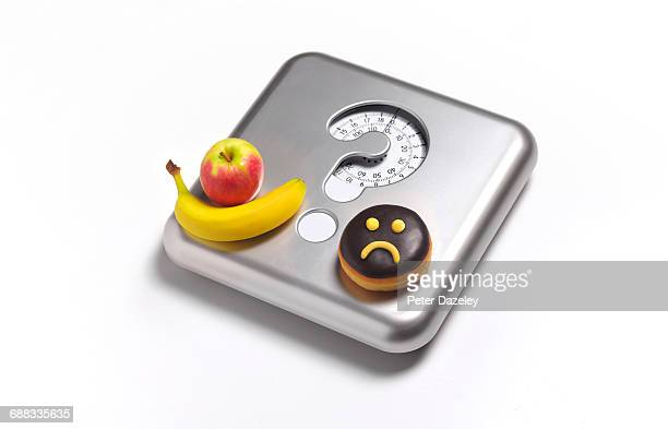 Unhappy doughnut and fruit on bathroom scales