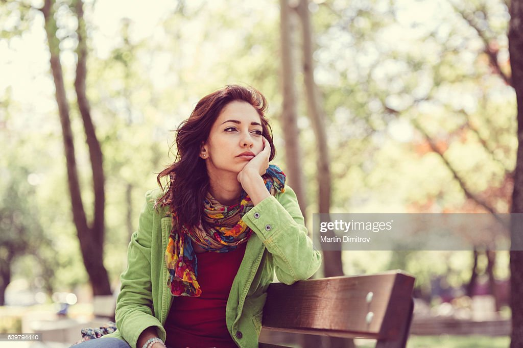 Unhappy girl sitting at bench : Stock Photo