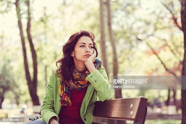 unhappy girl sitting at bench - loneliness stock pictures, royalty-free photos & images