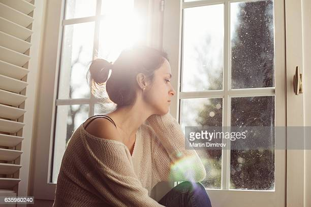 Unhappy housewife sitting near the window
