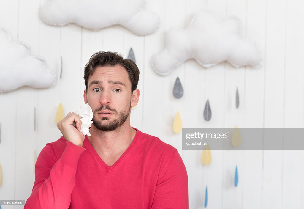 Unhappy ill man standing against cloudy background : Stock Photo