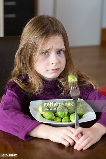Unhappy little girl with plate of Brussels sprouts
