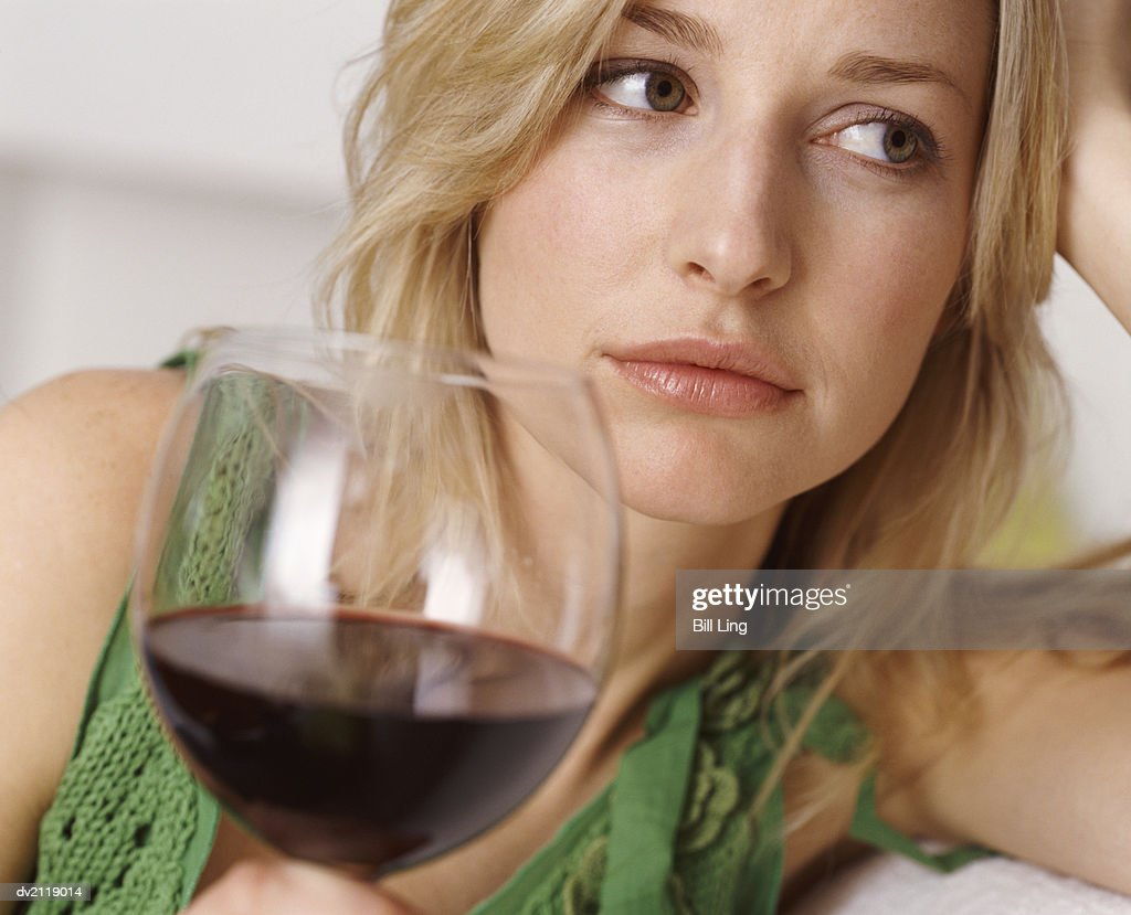 Unhappy Looking Woman Holding a Glass of Red Wine : Stock Photo