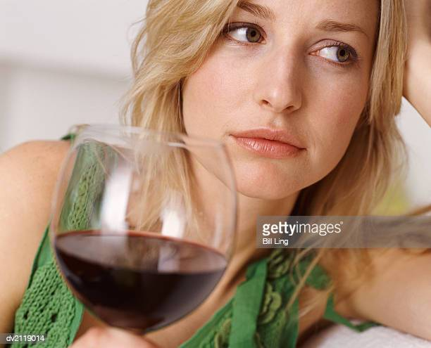 Unhappy Looking Woman Holding a Glass of Red Wine