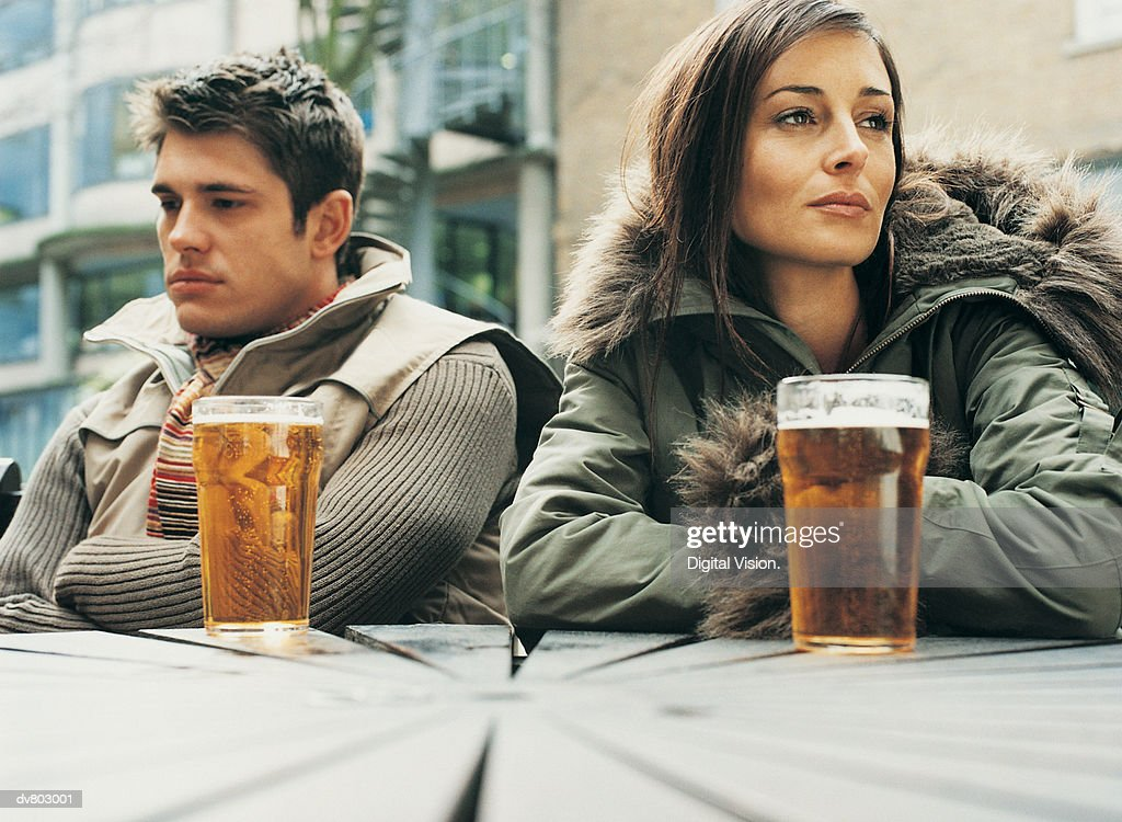 Unhappy Man and Woman Sitting Outside a Pub : Stock Photo