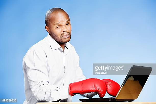 Unhappy man in boxing gloves tries, unsuccessfully, to use laptop