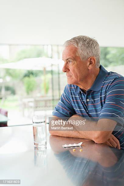 Unhappy man looking outside with pills on counter