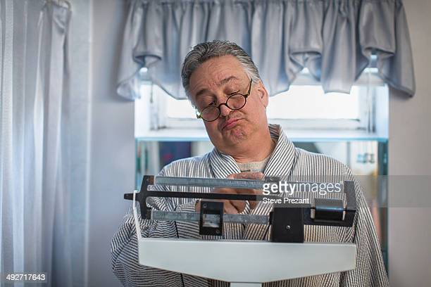 Unhappy mature man on bathroom weighing scales