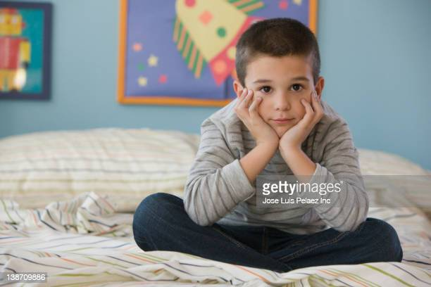 Unhappy mixed race boy sitting on bed