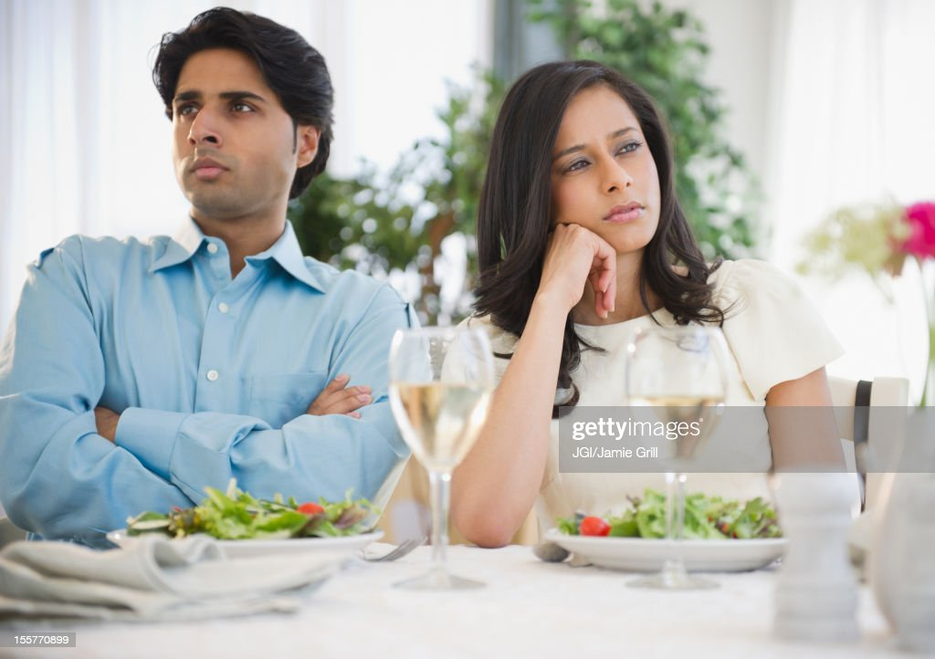 Unhappy mixed race couple dining together : Stock Photo