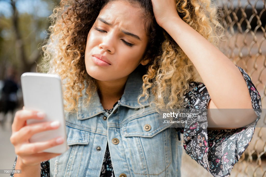 Unhappy Mixed Race woman texting on cell phone : Stock-Foto