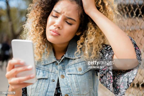 unhappy mixed race woman texting on cell phone - misnoegd stockfoto's en -beelden