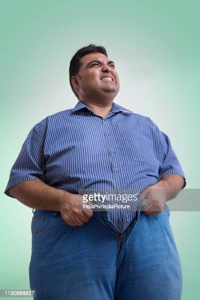 unhappy obese man trying hard to wear his pants not fitting his waist - man in tight pants stock photos and pictures