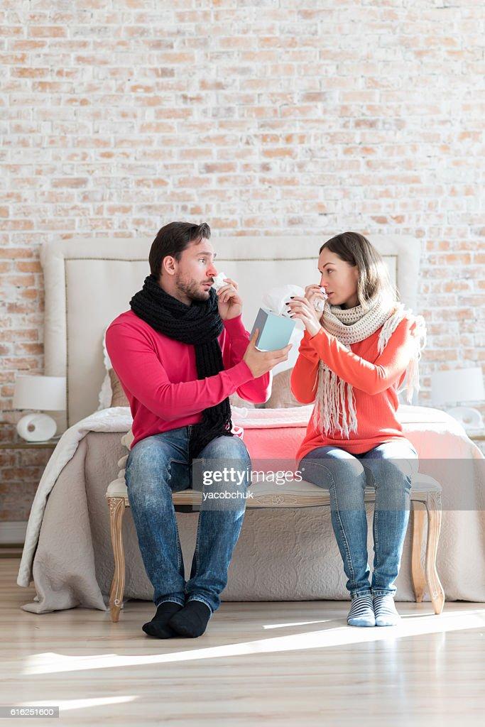 Unhappy sad man giving his girlfriend a box of tissues : Foto de stock