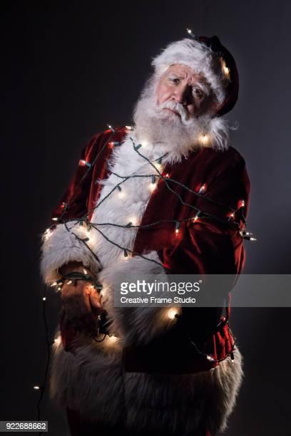 unhappy santa claus tied up / tangled in christmas lights - sapin de noel humour photos et images de collection