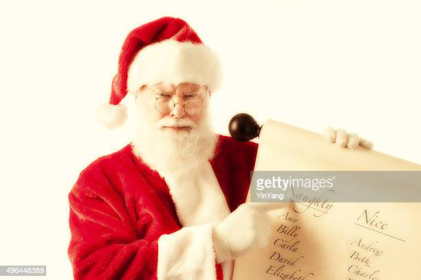 unhappy santa claus with naughter and nice name scroll - naughty santa stock photos and pictures