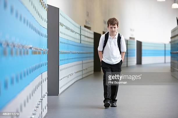 unhappy schoolboy walking alone in school corridor - vulnerability stock pictures, royalty-free photos & images