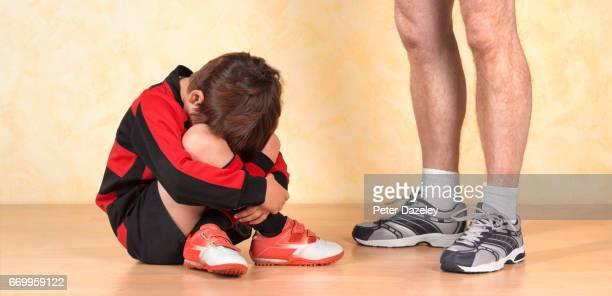 Unhappy schoolboy with sports teacher