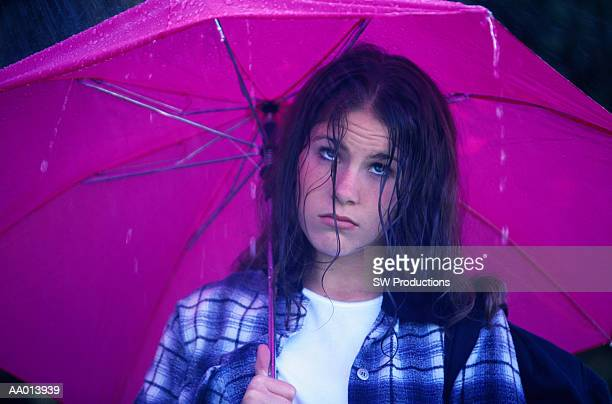 Unhappy Teen Girl Holding an Umbrella in the Rain