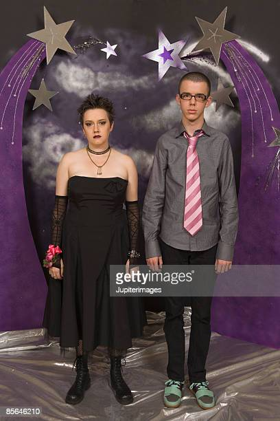 Unhappy teenage couple posing for prom portrait