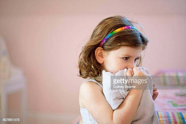 Unhappy three year old girl in bedroom holding comfort blanket to face